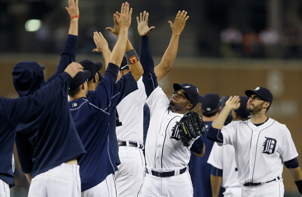 . Detroit Tigers center fielder Rajai Davis high-fives teammates after the Tigers\' 6-0 win over the Chicago Cubs in a baseball game, Tuesday, June 9, 2015, in Detroit. (AP Photo/Carlos Osorio)