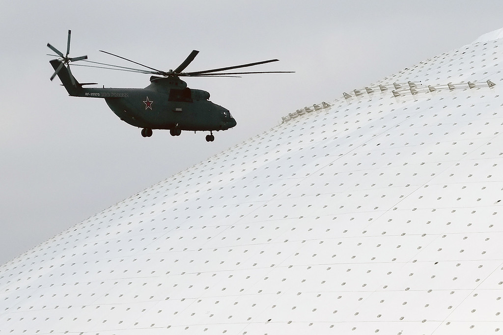 . A Russian military helicopter flies past the Bolshoy Ice Dome, site of the ice hockey competitions, ahead of the 2014 Winter Olympics, Wednesday, Feb. 5, 2014, in Sochi, Russia.  (AP Photo/J. David Ake)