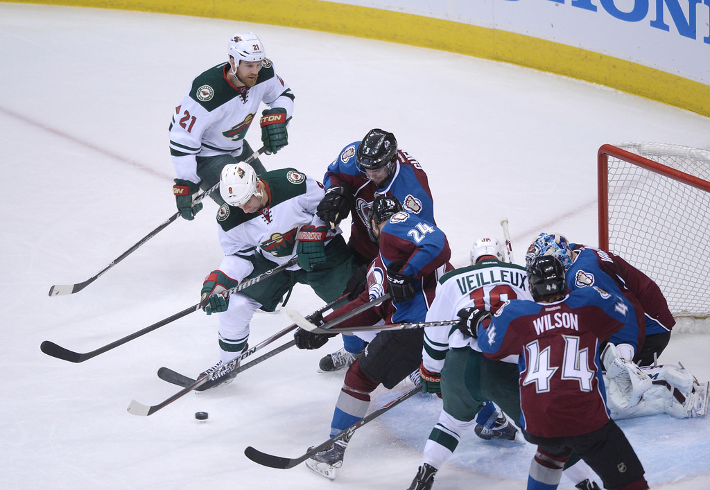 . Marc-Andre Cliche (24) and Nate Guenin (5) of the Colorado Avalanche battle Cody McCormick (8) of the Minnesota Wild for puck control during the first period of action.  (Photo by Karl Gehring/The Denver Post)