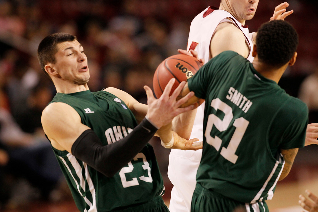 . Ohio forwards Ivo Baltic, front left, and Jon Smith battle each other for a rebound after Denver forward Blake Foeman missed a shot  in the first half of a first-round NIT college basketball game in Denver on Tuesday, March 19, 2013. (AP Photo/David Zalubowski)