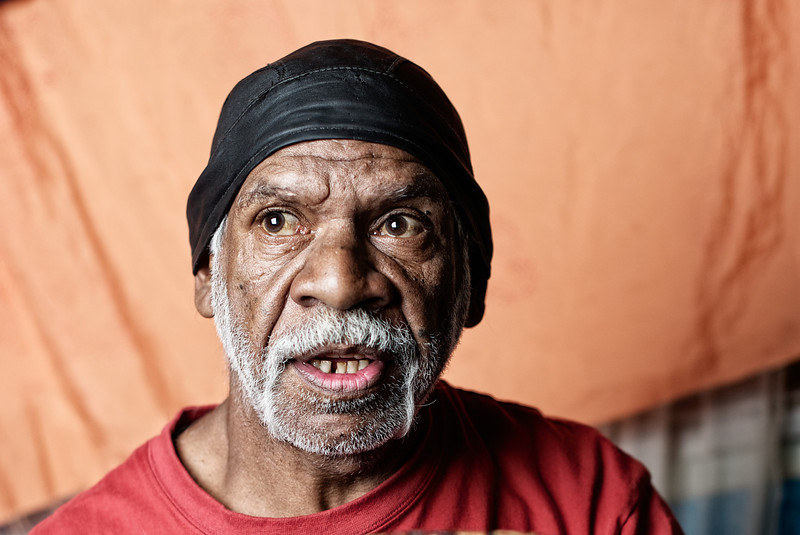 Indigenous Australian Elder looking up and to the side, on a blurred orange background