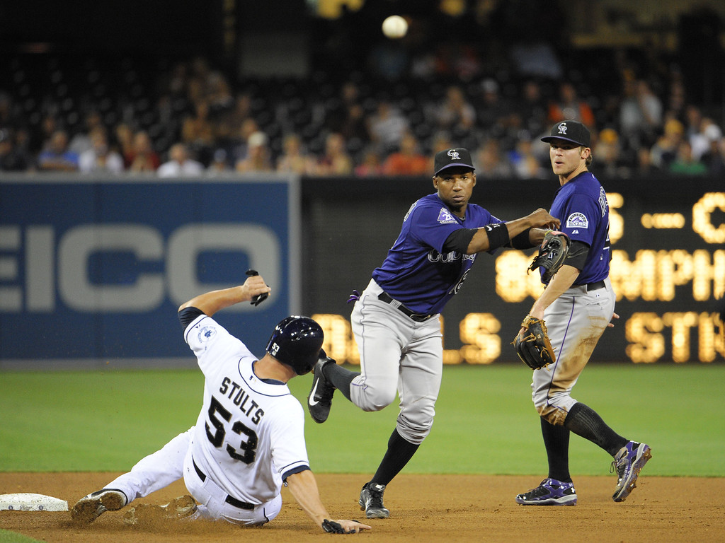 . Jonathan Herrera #18 of the Colorado Rockies throws over Eric Stults #53 of the San Diego Padres as he turns a double play during the fifth inning of a baseball game at Petco Park on July 9, 2013 in San Diego, California.  (Photo by Denis Poroy/Getty Images)