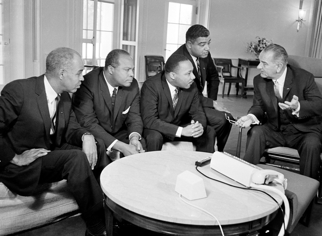 . U.S. President Lyndon B. Johnson, right, talks with civil rights leaders in his White House office in Washington, D.C., Jan. 18, 1964.  The black leaders, from left, are, Roy Wilkins, executive secretary of the National Association for the Advancement of Colored People (NAACP); James Farmer, national director of the Committee on Racial Equality; Dr. Martin Luther King Jr., head of the Southern Christian Leadership Conference; and Whitney Young, executive director of the Urban League.  (AP Photo)