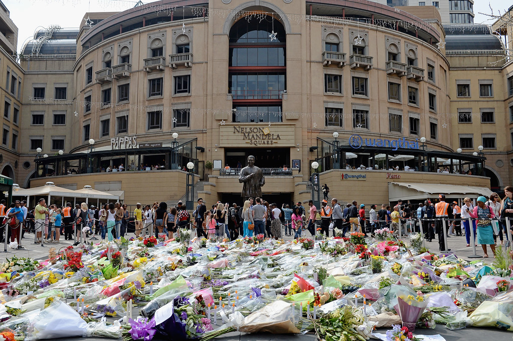 . South Africans lay flowers in Nelson Mandela Square as they pay respect to former President Nelson Mandela on December 7, 2013 in Johannesburg, South Africa. Mandela, also known as Madiba, passed away on the evening of December 5th, 2013 at his home in Houghton at the age of 95. Mandela became South Africa\'s first black president in 1994 after spending 27 years in jail for his activism against apartheid in a racially-divided South Africa (Photo by Jeff J Mitchell/Getty Images)
