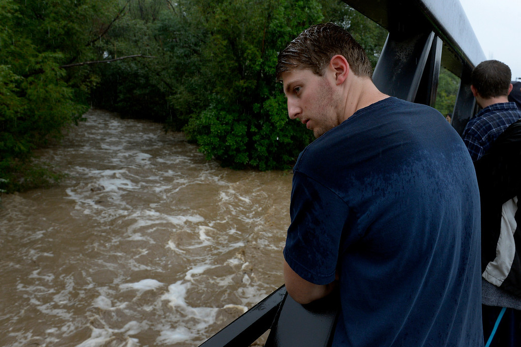 . BOULDER, CO. - SEPTEMBER12:  University of Colorado junior Bobby Crimi watches a raging  Boulder Creek from 28th Street in Boulder CO September 12, 2013. Record-breaking rain turned normally quiet creeks into raging, brown torrents that swept through Boulder on Thursday, flooding homes, swamping cars and closing roads and schools. (Photo By Craig F. Walker / The Denver Post)