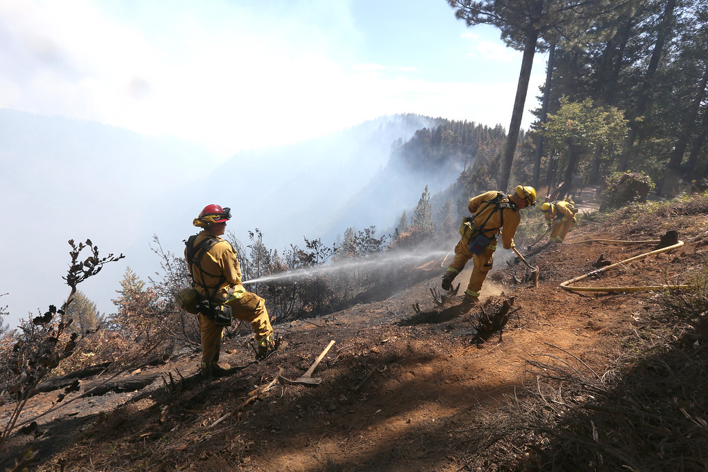 . Firefighters hose down hot spots of the King Fire near Pollack Pines, Calif., Monday, Sept. 15, 2014. The fire, which started Sunday has consumed more than 3,000 acres and forced the evacuation of dozens of homes. (AP Photo/Rich Pedroncelli)