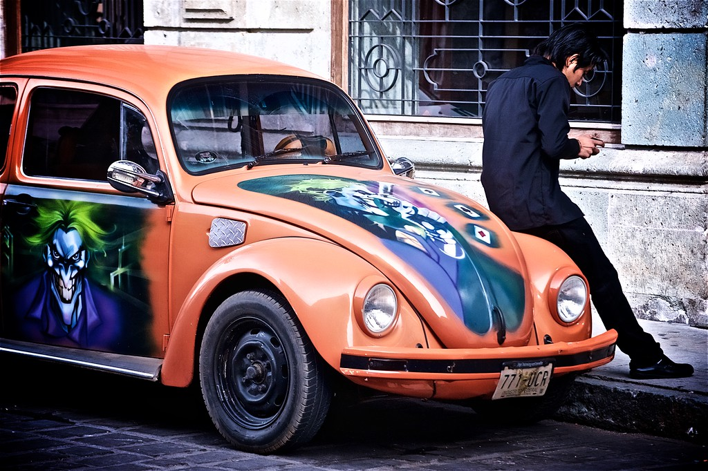 """A young man sits on the fender of his customized Volkswagen """"Voche"""" Beetle in Oaxaca, Mexico."""
