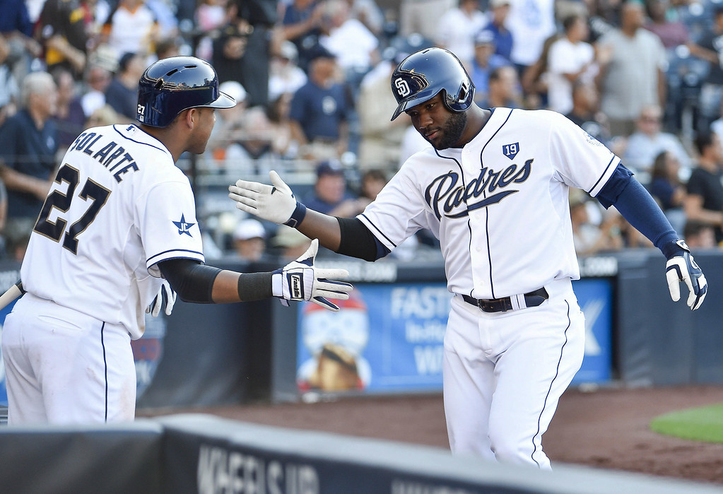 . SAN DIEGO, CA - AUGUST 13:  Abraham Almonte (R) #16 of the San Diego Padres is congratulated by Yangervis Solarte #27 after hitting a solo home run during the sixth inning of a baseball game against the Colorado Rockies at Petco Park on August 13, 2014 in San Diego, California.  (Photo by Denis Poroy/Getty Images)