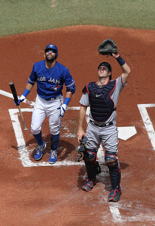 . Joe Mauer of the Minnesota Twins and Jose Bautista  of the Toronto Blue Jays watch a foul ball go out of play. (Photo by Tom Szczerbowski/Getty Images)