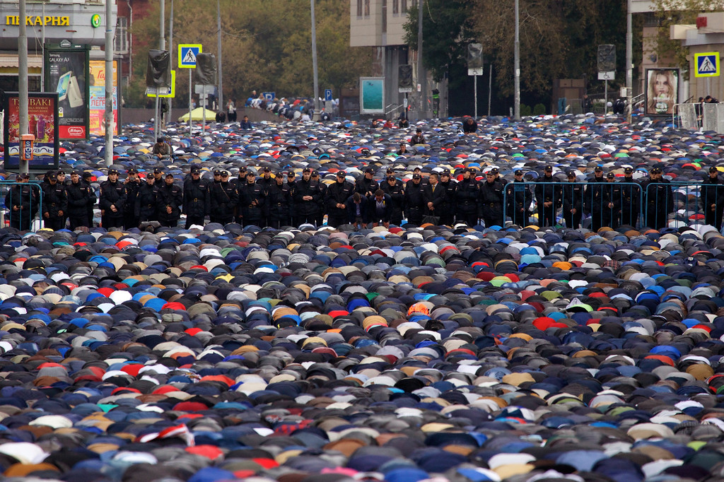 . Russian police officers stand guard as muslims pray outside a mosque during celebrations of Eid al-Adha, a feast celebrated by Muslims worldwide, which Muslims in Russia call Kurban-Bairamin Moscow, Russia, on Monday, Sept. 12, 2016. (AP Photo/Ivan Sekretarev)