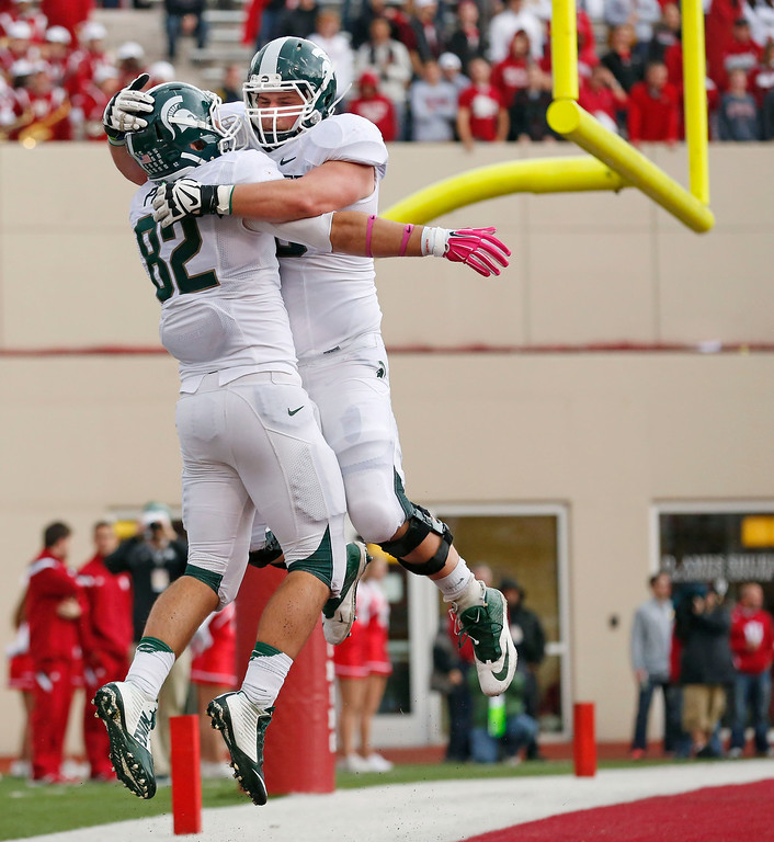. Michigan State tight end Josiah Price (82) celebrates his touchdown with Michigan State offensive lineman Travis Jackson (63) during the first half of an NCAA college football game in Bloomington, Ind., Saturday, Oct. 18, 2014. Michigan State won the game 56-17. (AP Photo/Sam Riche)