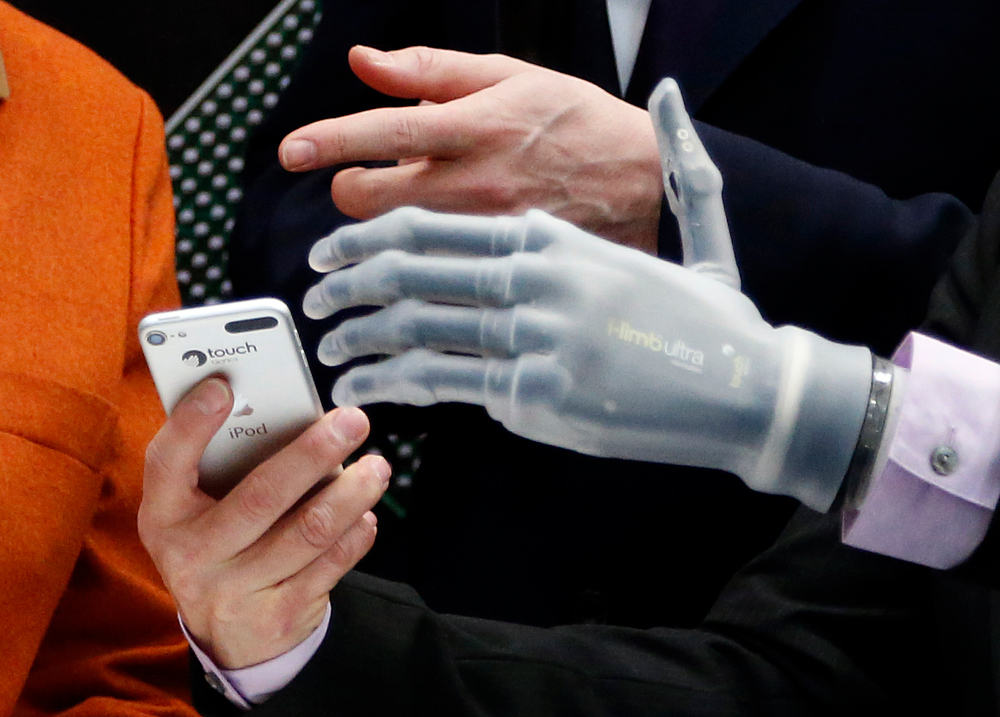 . The hands of Claudia Breidbach, right, demonstrates the use of her bionic hand, which is steerable by a mobile phone or iPod via Bluetooth to  British Prime Minister David Cameron  during the opening day of  the computer fair CeBIT in Hannover, Germany, Monday, March 10, 2014. Great Britain is the partner country at this year\'s CeBIT which runs through March 14.(AP Photo/Frank Augstein)