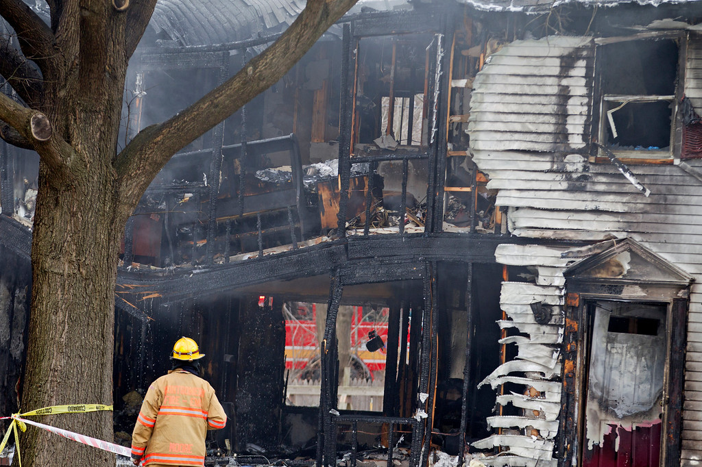 . A firefighter stands outside a smoldering house where a small private jet crashed in Gaithersburg, Md., Monday, Dec. 8, 2014. A woman and her two young sons inside the home and three people on the aircraft were killed, authorities said. (AP Photo/Jose Luis Magana)