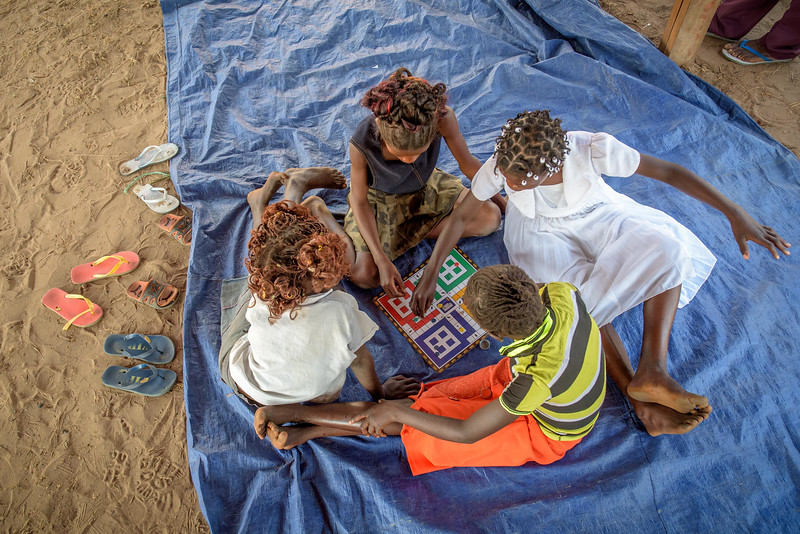 """Kapinga Alphoncine, 13 yr-old girl. (white dress and white beads in hair), plays Game of Six with friends at Nganza Child Friendly Space.   Kapinga lives with her widowed grandmother, Kapinga Godelive, 66 and her 3 brothers: 1-Francois Ngondo, 14 2-Mbuyamba Phillip, 9 3-Beya Honore, 6 Kananga, DRC Democratic Republic of Congo.  CFS Kapinga also love the Nganza Child Friendly Space (CFS.) There she plays games, soccer and dances but also learns things like how to mend her clothes. """"The CFS is a good place. I've learned to mend my clothes. And I like to play soccer.""""  In the afternoon there, Kapinga and 3 friends play a dice game called Game of Six. There are about 1,985 children who attend this CFS, in two sessions. In addition to games, the """"animators,"""" volunteers who supervise the children, also teach the children about children's rights, health and skills like mending their clothes.  The biggest challenge at World Vision's CFS' is providing psycho-social care for former child soldiers.  We have an interview with Chief Animator, Jean Nicolas Kankonde, 53. Kankonde says there are two kinds of former militia chidren. """"There are two kinds of children. (Some) easily accept it and learn to become collaborative. But some think that if they admit being in a militia, they will be turned into the government."""" Here, only 15 of the 1900+ children have admitted to being in militias. 11 boys and 4 girls.  The Chief Animator says to make true progress here, children need to study, elementary education needs to be free and teachers need to be paid well.  Inside Kapinga's four-room house the walls are paint splattered. There is little furniture except for two small tables and an old cabinet. On top sits a dusty old television. A peek behind reveals that it has no cord. Kapinga sits on a low, wooden bench against one wall reading an old school exercise book of English lessons. """"Good morning my friends, good morning.""""  Her English is good in spite of a mispronunciation here and ther"""