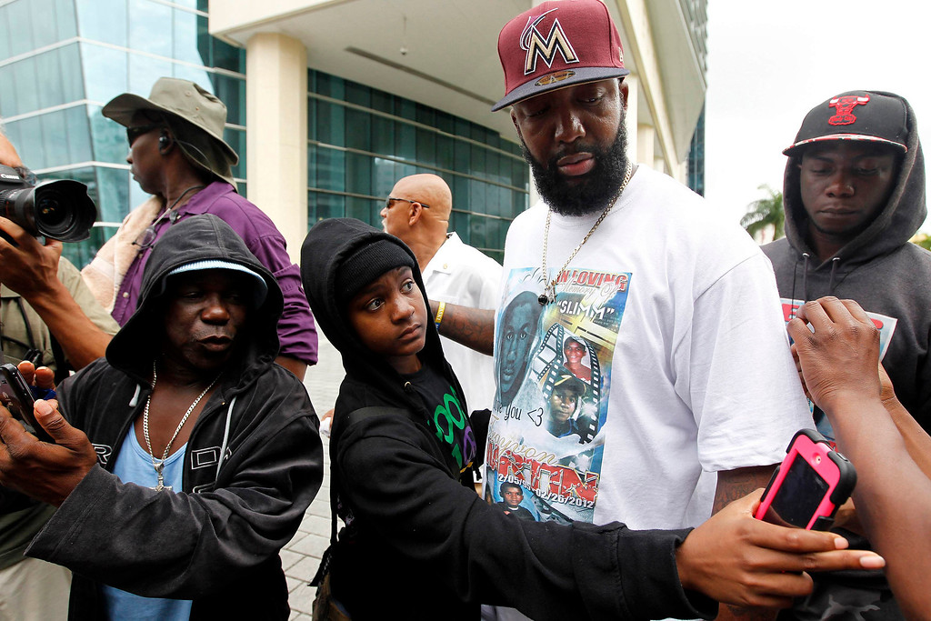 . Tracy Martin (2nd R), father of Trayvon Martin, is surrounded by members of the crowd before a group photo during a rally for his son in Miami, Florida July 20, 2013. Trayvon Martin\'s parents were due to lead demonstrations in New York and Miami on Saturday, as protesters across the country rallied to express anger over the acquittal of George Zimmerman, the man who shot and killed the unarmed black teenager. REUTERS/Andrew Innerarity