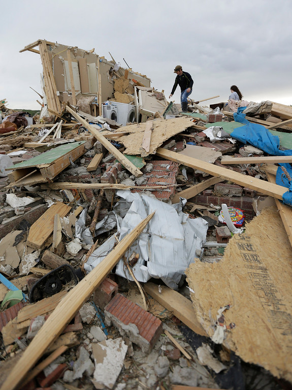. Austin Hargrove, left, and Haley Hracke, right, help recover personal items from a friends home that was destroyed by Sunday\'s tornado, Tuesday, April 29, 2014, in Vilonia, Ark.  (AP Photo/Eric Gay)