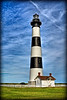 Black and white striped lighthouse in North Carolina near the beach.