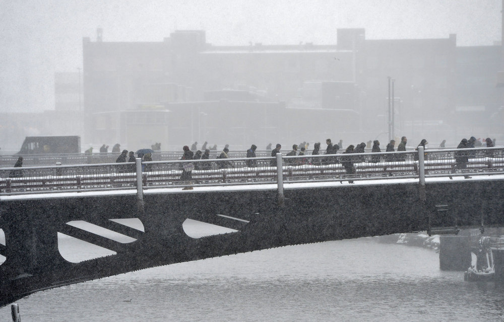 Description of . Pedestrians cross the Chicago River on March 5, 2013 in Chicago, Illinois. The worst winter storm of the season is expected to dump 7-10 inches of snow on the Chicago area with the worst expected for the evening commute.  (Photo by Brian Kersey/Getty Images)