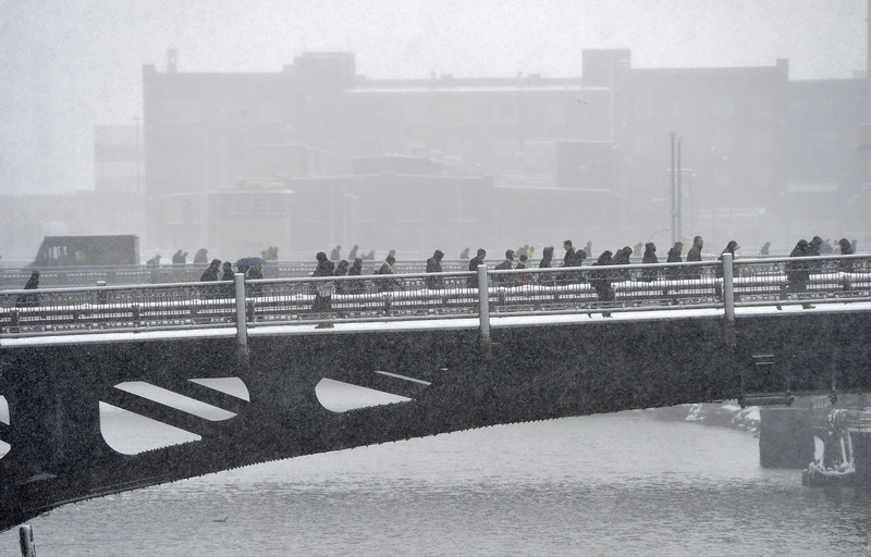 . Pedestrians cross the Chicago River on March 5, 2013 in Chicago, Illinois. The worst winter storm of the season is expected to dump 7-10 inches of snow on the Chicago area with the worst expected for the evening commute.  (Photo by Brian Kersey/Getty Images)