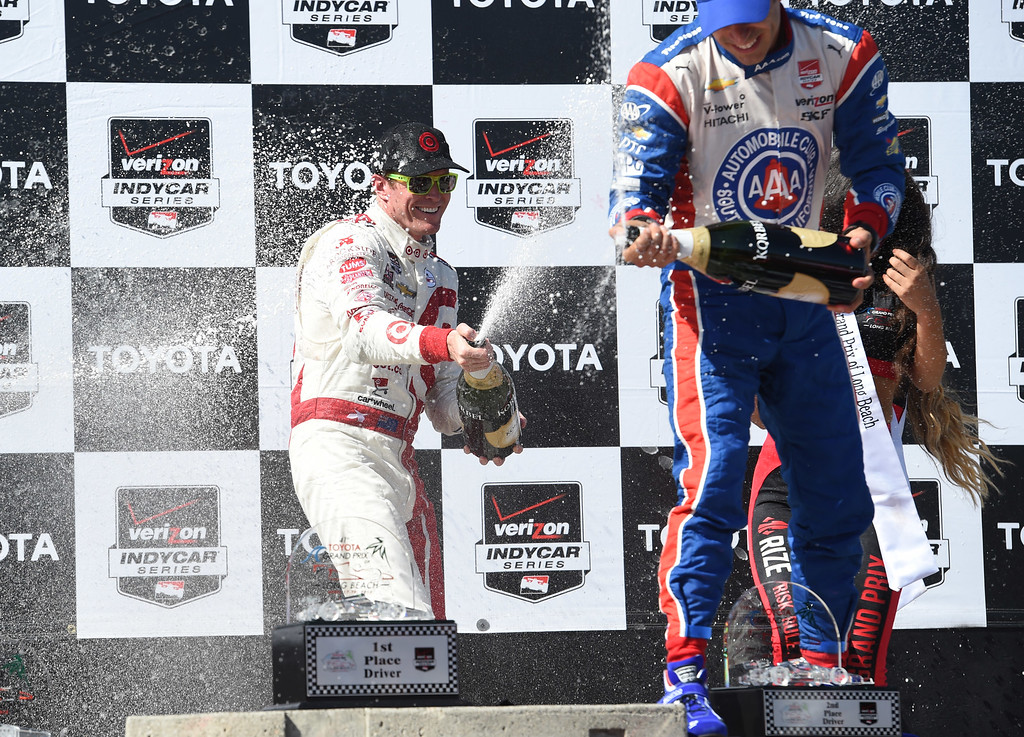 . Toyota Grand Prix of Long Beach winner Scott Dixon, left, sprays champagne on 2nd place finisher Helio Castroneves, on the winners podium.  Long Beach  Calif., Sunday,  April,19, 2015.     (Photo by Stephen Carr / Daily Breeze)