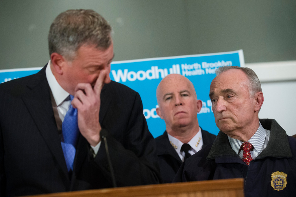 . NYPD Commissioner Bill Bratton, right, stands beside Mayor Bill de Blasio as he wipes his eye during a news conference at Woodhull Medical Center, Saturday, Dec. 20, 2014, in New York.  An armed man walked up to two New York Police Department officers sitting inside a patrol car and opened fire Saturday afternoon, killing one and critically wounding a second before running into a nearby subway station and committing suicide, police said. (AP Photo/John Minchillo)