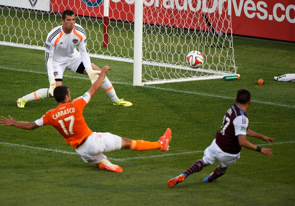 . COMMERCE CITY, CO - JUNE 01: Colorado Rapids midfielder Dillon Serna (17) takes a shot on Houston Dynamo goalkeeper Tally Hall (1) during the second half asHouston Dynamo midfielder Servando Carrasco (17) defends on the play June 1, 2014 at Dick\'s Sporting Goods Park. His shot sailed high and right. (Photo by John Leyba/The Denver Post)