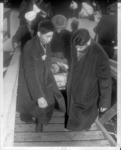 """""""Stretcher Case -- Saido Matsuma, one of 676 Japanese leaving U. S. for Japan, is carried aboard ship by other Japanese repatriates.  There are 16 other stretcher cases.""""--caption on photograph"""