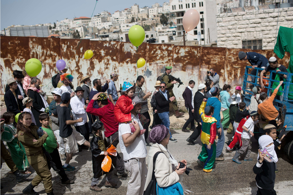 . Israeli settlers, some dresses up in masks, take part in a parade to celebrate the Jewish holiday of Purim along al-Shuhada Street, in the West Bank town of Hebron, on March 16, 2014. The carnival-like Purim holiday is celebrated with parades and costume parties to commemorate the deliverance of the Jewish people from a plot to exterminate them in the ancient Persian Empire 2,500 years ago, as recorded in the Biblical Book of Esther. (MENAHEM KAHANA/AFP/Getty Images)