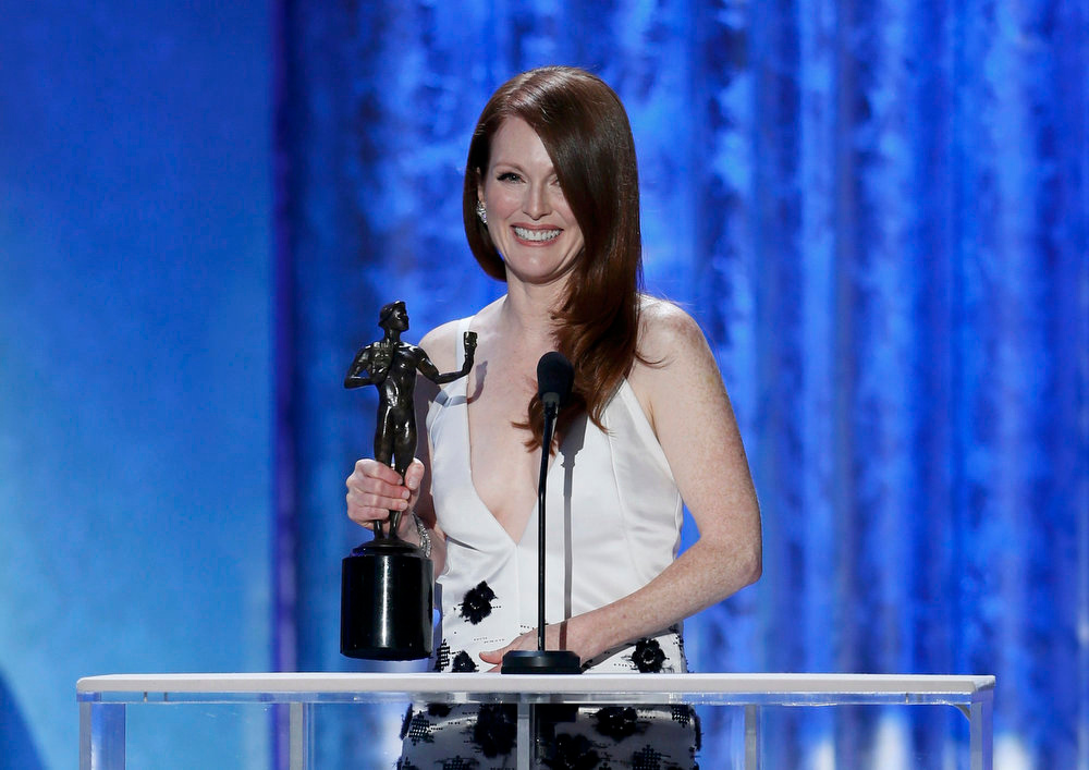 ". Julianne Moore accepts the award for outstanding female actor in a tv movie or miniseries for ""Game Change\"" at the 19th annual Screen Actors Guild Awards in Los Angeles, California January 27, 2013.   REUTERS/Lucy Nicholson"
