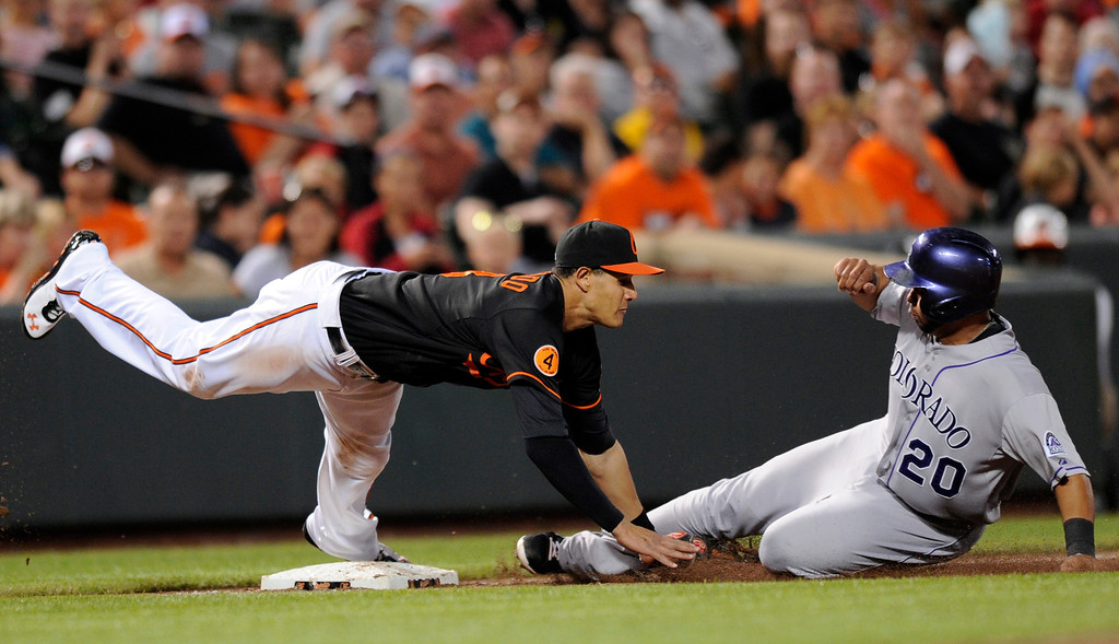 . Colorado Rockies\' Wilin Rosario (20) slides into third safely on a wild pitch against the Baltimore Orioles third baseman Manny Machado (13) during the fifth inning of a baseball game, Friday, Aug. 16, 2013, in Baltimore. (AP Photo/Nick Wass)