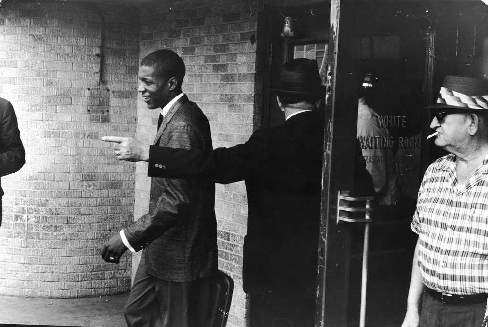 Description of . An unidentified young Black 'Freedom Rider' is told to leave a segregated 'white' waiting room at a bus depot in Jackson, Mississippi, May 26, 1961. The Freedom Riders traveled from Montgomery, Alabama to Mississippi to protest segregation in public bus depots. February 4, 2013 will mark 100 years since the birth of civil rights activist Rosa Parks who was brought to attention when in 1955 she refused to give up her seat on a bus for a white passenger in Alabama. The US Postal service are due to unveil a special stamp which features her in an unveiling ceremony scheduled on her birthday at museums in both Detroit and Michigan.  (Photo by Express Newspapers/Getty Images)