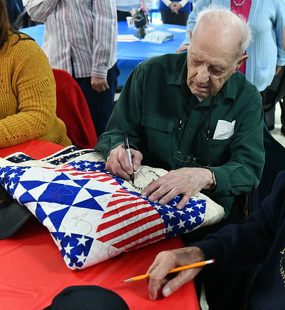 12/7/2019 Mike Orazzi | StaffrAnthony D'Angelo signs the WWII quilt while at the Bristol American Legion Seicheprey Post 2 on Saturday morning for the Pearl Harbor Day ceremony.