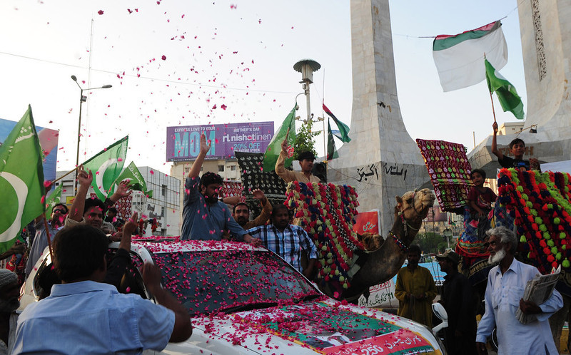 . Supporters of Pakistan Muslim league Functional (PML-F) shower rose petals on candidate of national assembly Kamran Tessori (C) during an election campaign in Karachi on May 4, 2013. A Pakistani candidate running for parliament in next week\'s historic election was injured on Saturday as his vehicle hit a roadside bomb in the troubled northwest, officials said.   ASIF HASSAN/AFP/Getty Images