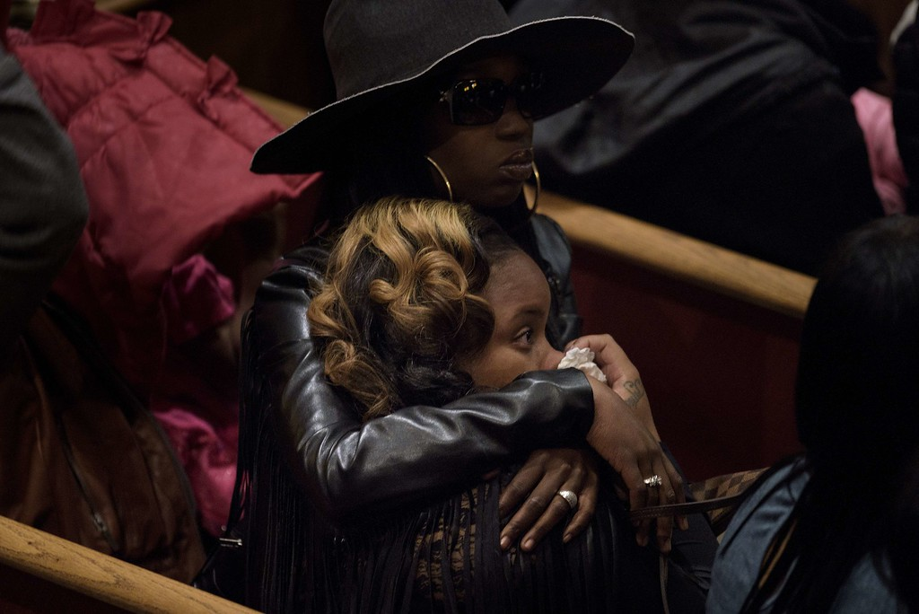 . People embrace while waiting for Freddie Gray\'s funeral at New Shiloh Baptist Church April 27, 2015 in Baltimore, Maryland. Mourners gathered in large numbers at the funeral of Gray, the 25-year-old black man who died April 19 after an encounter April 12 with police left him with grave spinal injuries. BRENDAN SMIALOWSKI/AFP/Getty Images