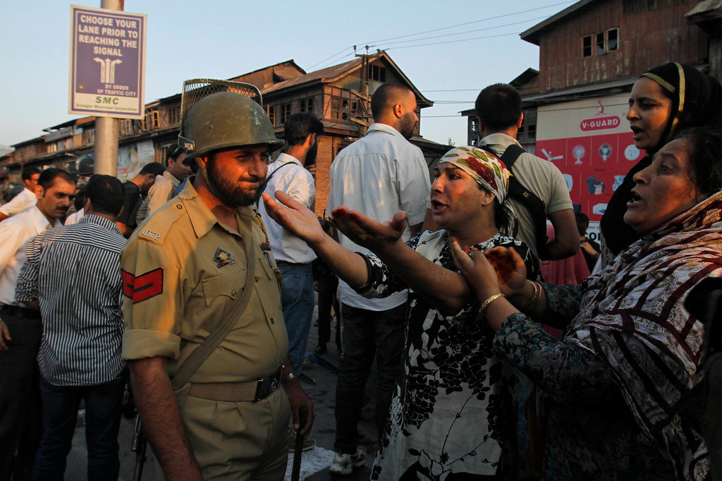 . Kashmiri women react, as they talk to a policemen after paramilitary troops opened fire on a car when the driver allegedly failed to stop at a police barricade in Srinagar, India, Saturday, Sept. 7, 2013. A protest erupted Saturday after Indian police said they killed two alleged militants and two civilians in the disputed Himalayan territory of Kashmir, while authorities maintained tight security for a classical music concert being staged amid separatist objections. The driver was hospitalized in critical condition. (AP Photo/Mukhtar Khan)