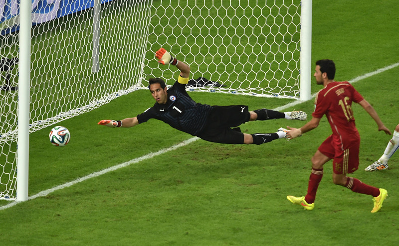 . Spain\'s midfielder Sergio Busquets (C) misses a shot on goal as Chile\'s goalkeeper and captain Claudio Bravo (L) defends during a Group B football match between Spain and Chile in the Maracana Stadium in Rio de Janeiro during the 2014 FIFA World Cup on June 18, 2014. (YASUYOSHI CHIBA/AFP/Getty Images)