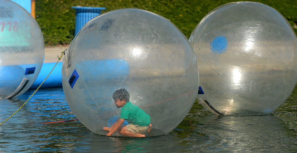 . A boy tries to stand in an inflatable bubble during Indy car practice in Long Beach, CA on Friday, April 17, 2015. People were able to spend a few minutes in a bubble and try to maneuver in Rainbow Lagoon. The 40th annual Toyota Grand Prix of Long Beach kicked off with practices for all of the racing divisions. (Photo by Scott Varley, Daily Breeze)