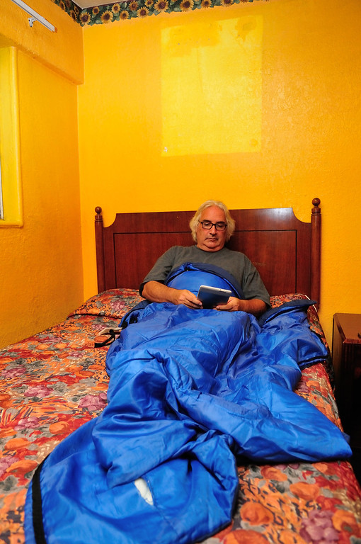 . Wrapped in a sleeping bag and reading in bed below a missing picture at the El Capitan Motor Inn.Photo by Thomas Wasper for the Press Telegram