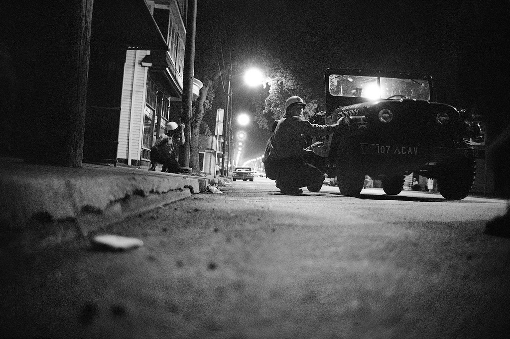 . City police and National Guardsmen take cover behind jeep and lamp pole on a report of sniper fire in riot area in Cleveland, Ohio, July 20, 1966. Reports of violence were numerous into the fifth night of unrest in Cleveland. (AP Photo)