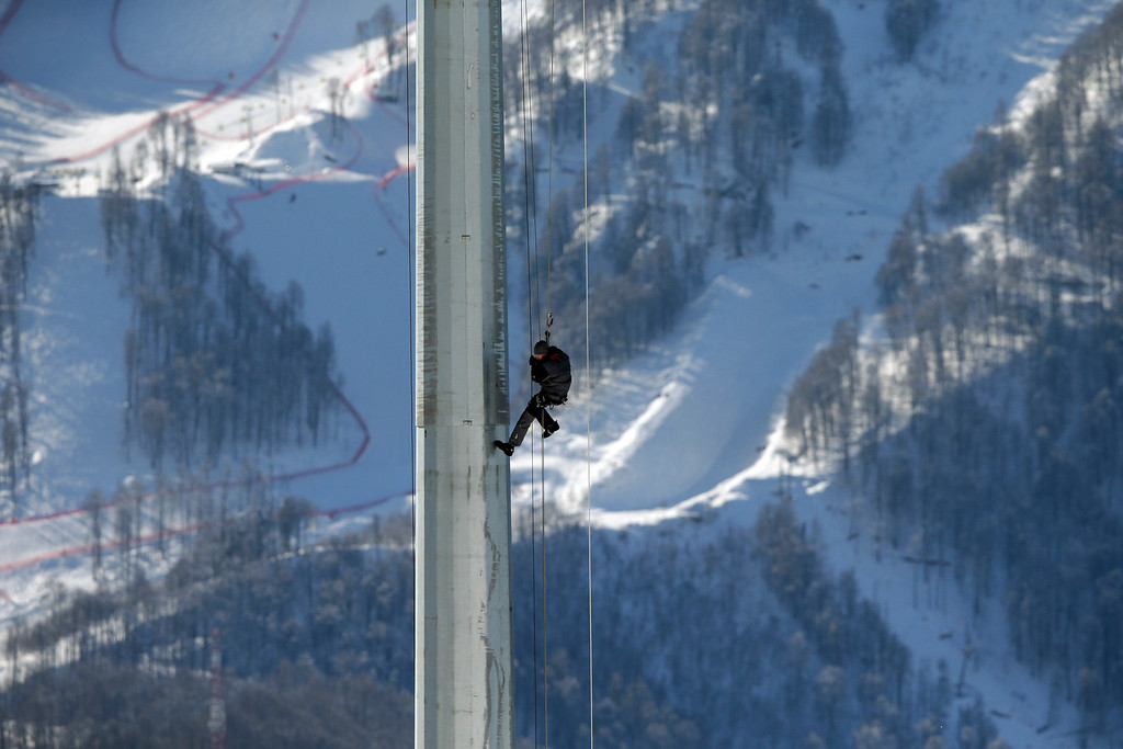 . A worker climbs a floodlight pole of the Biathlon stadium, at the 2014 Winter Olympics, Tuesday, Feb. 4, 2014, in Krasnaya Polyana, Russia. (AP Photo/Lee Jin-man)