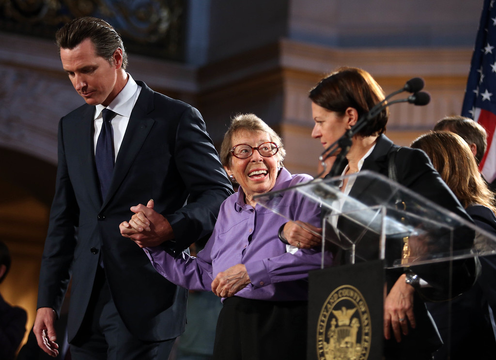 . Former San Francisco mayor Gavin Newsom, left, escorts longtime gay rights activist Phyllis Lyon, center, to her seat as they celebrate at City Hall in San Francisco, Calif., on Wednesday, June 26, 2013. Lyon and her partner Del Martin, who died in 2008, founded the Daughters of Bilitis, the nation\'s first lesbian social and political organization, in San Francisco in 1955.The U.S. Supreme Court dismissed California\'s Proposition 8 and declared the 1996 Defense of Marriage Act unconstitutional. (Jane Tyska/Bay Area News Group)