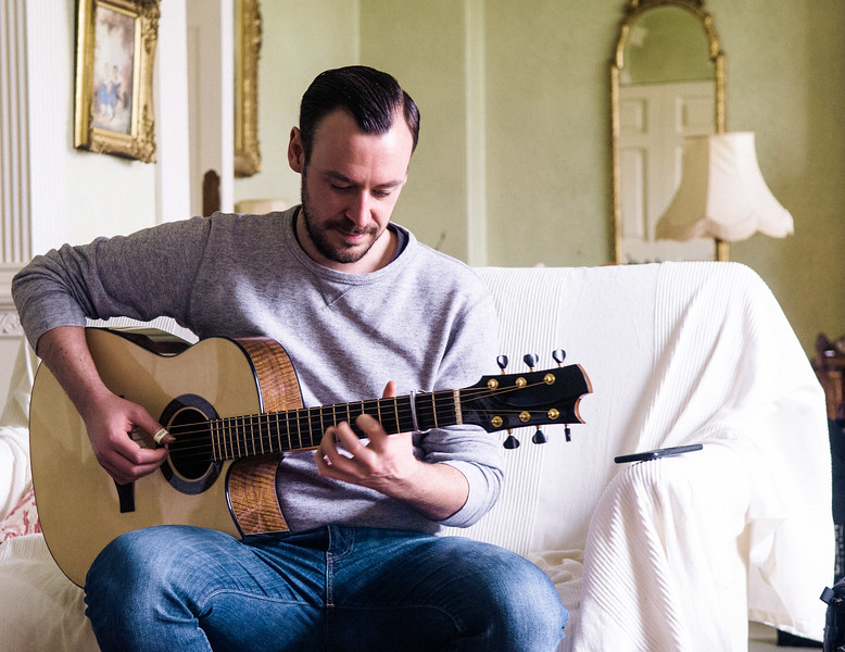 Man playing Acoustic Guitar Indoors