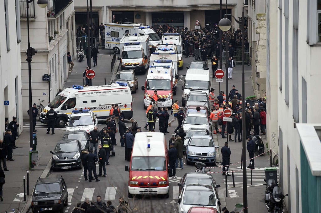 . A general view shows firefighters, police officers and forensics gathered in front of the offices of the French satirical newspaper Charlie Hebdo in Paris on January 7, 2015, after armed gunmen stormed the offices leaving twelve dead. Heavily armed gunmen shouting Islamist slogans stormed a Paris satirical newspaper office on January 7 and shot dead at least 12 people in the deadliest attack in France in four decades. Police launched a massive manhunt for the masked attackers who reportedly hijacked a car and sped off, running over a pedestrian and shooting at officers. AFP PHOTO / MARTIN BUREAU/AFP/Getty Images