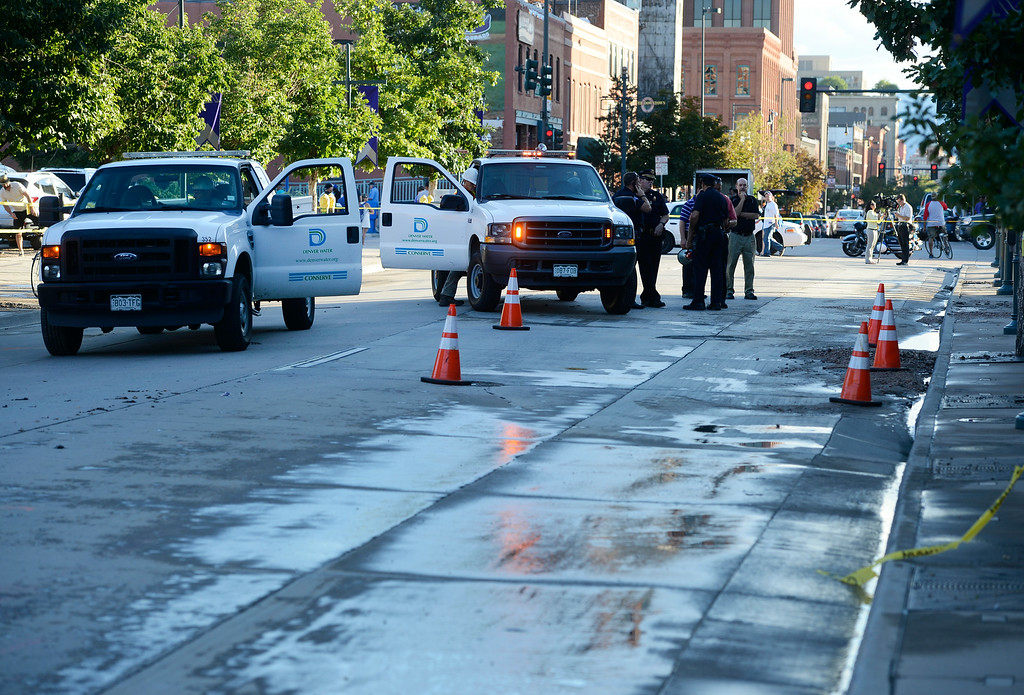 . DENVER, CO. - AUGUST 16:  Denver Police officers, Denver Water crews and Colorado Rockies officials stand along Blake St. in front of Coors Field Saturday evening, August 16, 2014. The game scheduled against the Cincinnati Reds was cancelled due to a water main break along Blake St, cutting off water supply to the stadium. (Photo By Andy Cross / The Denver Post)