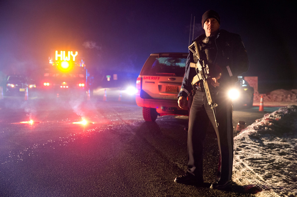 """. Sgt. Tom Hutchison stands in front of an Oregon State Police roadblock on Highway 395 between John Day and Burns by Oregon State police officers Tuesday, Jan. 26, 2016. Authorities say shots were fired Tuesday during the arrest of members of an armed group that has occupied a national wildlife refuge in Oregon for more than three weeks. The FBI said authorities arrested Ammon Bundy, 40, his brother Ryan Bundy, 43, Brian Cavalier, 44, Shawna Cox, 59, and Ryan Payne, 32, during a traffic stop on U.S. Highway 395 Tuesday afternoon. Authorities said another person, Joseph Donald O\'Shaughnessy, 45, was arrested in Burns. In a statement, the FBI said one individual \""""who was a subject of a federal probable cause arrest is deceased.\""""   (Dave Killen/The Oregonian via AP)"""