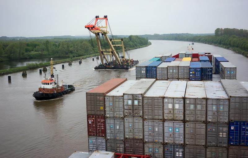 Containerschiff im Nord Ostsee Kanal mit Schwimmkran ENAK und Schlepper Steinbock