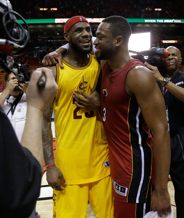 . Cleveland Cavaliers forward LeBron James (23) and Miami Heat guard Dwyane Wade talk following an NBA basketball game, Thursday, Dec. 25, 2014, in Miami. The Heat defeated the Cavaliers 101-91. (AP Photo/Lynne Sladky)