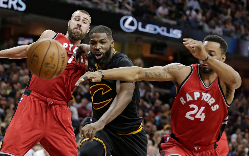 . Toronto Raptors\' Jonas Valanciunas, left to right, from Lithuania, Cleveland Cavaliers\' Tristan Thompson and Toronto Raptors\' Norman Powell battle for a loose ball in the first half of an NBA basketball game, Wednesday, April 12, 2017, in Cleveland. (AP Photo/Tony Dejak)
