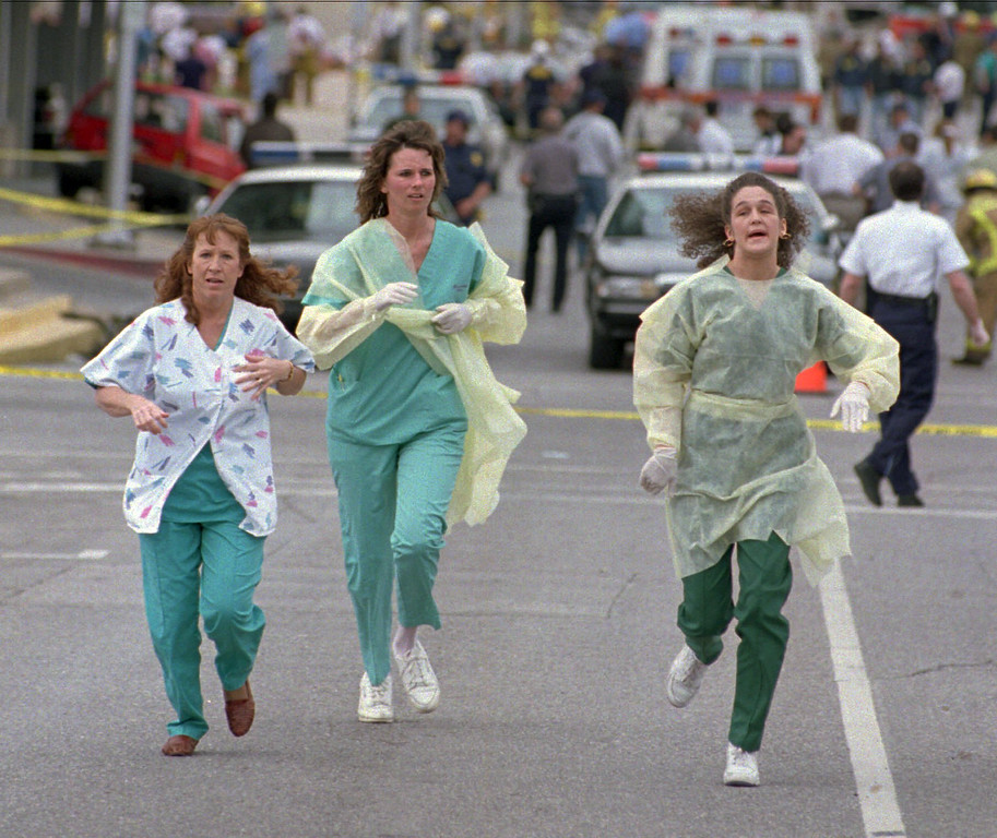 . FILE - In this April 19, 1995 file photo, medical assistants, Janet Froehlich, left, Wilma Jackson and Kerri Albright run from the Alfred Murrah Federal Building after being told another bomb device had been found in Oklahoma City. The blast killed 168 people - including 19 children - injured hundreds more and caused hundreds of millions of dollars in damage to structures and vehicles in the downtown area. (AP Photo/David J. Phillip)