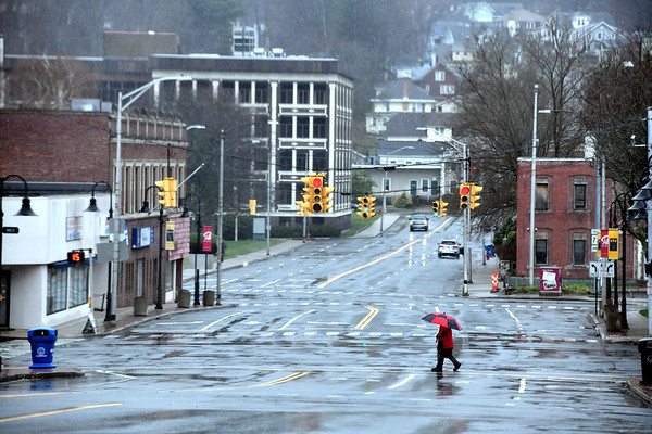 4/9/2020 Mike Orazzi | StaffrA pedestrian cross a nearly empty Main Street in downtown Bristol on Thursday morning.